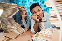 Ethnic indian mixed race guy and white girl surrounded by books in library. Students are looking at books. Ethnic indian mixed race guy and white girl sitting Royalty Free Stock Photos