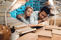 Ethnic indian mixed race guy and white girl surrounded by books in library at night. Students are sleeping. Ethnic indian mixed race guy and white girl sitting Stock Photography