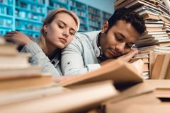 Ethnic indian mixed race guy and white girl surrounded by books in library at night. Students are sleeping. Ethnic indian mixed race guy and white girl sitting Stock Image
