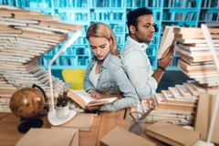 Ethnic indian mixed race guy and white girl surrounded by books in library. Students are reading books. stock photo