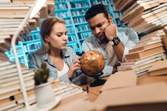 Ethnic indian mixed race guy and white girl surrounded by books in library. Students are using globe. royalty free stock photos