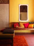 Ethnic Interior, old Malay house with cat. A photograph showing the inside living room of an old wooden malaysia house, with colorful wood walls and furniture stock photos