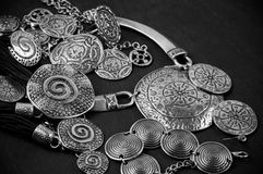 Ethnic jewelry. Collection of silver ethnic jewelry on black wooden background royalty free stock image
