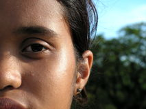 Ethnic malay teen face. A malay lady looking straight at the camera, partial face shot of eye and nose. Eye-level, background is some trees and sky Stock Images