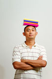 Ethnic male college student with books on head Stock Photo