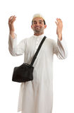 Ethnic man with arms raised in praise. Ethnic miixed race man wearing white embroidered robe  and topi hat and carrying black shoulder bag and arms raised in Royalty Free Stock Photography