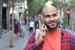 Ethnic man calling by phone outdoors stock photo