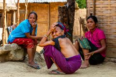 Ethnic minority nomadic women Laos. Bachong Nay,, Laos - April 10, 2018: Three women pertaining to a Lao ethnic minority sitting in front of a bamboo house in a Stock Images