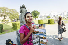 An ethnic minority woman sell postcard in a center park in Yangon Royalty Free Stock Photos