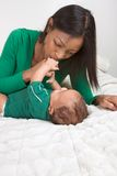 Ethnic mother playing with her baby boy son on bed Royalty Free Stock Images