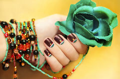 Ethnic motifs. Ethnic motifs on the nails female young hands with beaded bracelet with turquoise rose on a yellow background stock photo