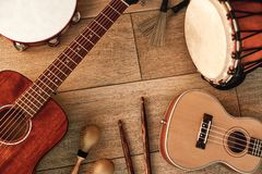Ethnic musical instruments set: tambourine, wooden drum, brushes, wooden sticks, maracas and guitars laying on wooden. Floor. Music concept. Musical instruments stock photos