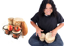 Ethnic musician. Funky long haired ethnic African American and Native Indian male playing bongo drums on a white background with other latin instruments on the Royalty Free Stock Photography