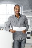 Ethnic office worker smiling. Portrait of ethnic office worker smiling, standing with document handheld, looking at camera stock photos