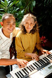 Ethnic old mother and son happy playing piano Stock Image
