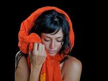 Ethnic portrait of a beautiful woman. Ethnic portrait of a beautiful brunette model wrapped in an orange scarf Stock Image