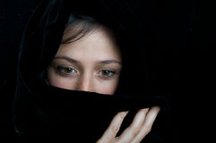 Ethnic portrait of a beautiful woman. Beautiful ethnic woman with sad eyes, wrapped in a black scarf Stock Photography