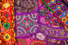 Ethnic Rajasthan cushion and belts. Colorful ethnic Rajasthan cushion cover and belts with mirrors on flea market in India stock images