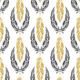 Ethnic seamless pattern with beauty feathers. Vintage tribal feather in black and gold colors Stock Photo