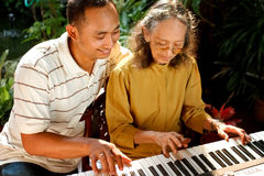 Ethnic senior woman and young man playing piano