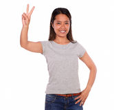 Ethnic smiling young woman celebrating a victory. Portrait of an ethnic smiling young woman on blue jeans and gray t-shirt looking at you and celebrating a royalty free stock images