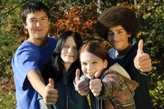 Ethnic teen thumbs up. Teens of various ethnic backgrounds outdoors giving a thumbs up. Focus on teen girl second from right stock images