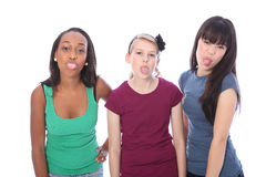 Ethnic teenage girl friends fun tongues out. Tounges sticking out in fun gesture for three pretty young teenager girl friends a blonde caucasian student, an Royalty Free Stock Images