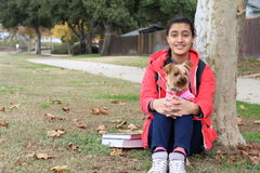 Ethnic teenage girl playing with a dog under a tree in the park with books and school backpack.  Royalty Free Stock Photos