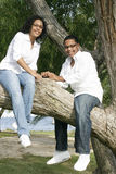 Ethnic teens in tree. Attractive ethnic siblings outside at a park in a tree Stock Image