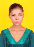 Ethnic woman. Beautiful young mixed race asian / caucasian woman model posing with a green dress on a yellow background Royalty Free Stock Images