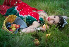 Ethnic woman with apples on grass. Ethnic woman girl with apples are resting on grass with basket with apples . Crown on head tribal jewelry rings bracelets stock photo