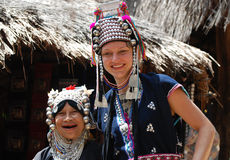 Ethnic woman and Caucasian girl dressed alike. Elderly, ethnic Hmong woman and young pretty Caucasian girl in northern Thailand, Chiang Mai province, Golden stock image