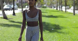 Ethnic woman in gray sportswear. Young attractive ethnic woman in gray sportswear looking at camera and standing on green grass in sunny park stock footage