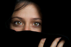 Ethnic woman hiding her face. Beautiful image of an ethnic woman hiding her face behind a scarf Royalty Free Stock Photo