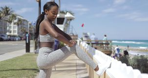 Ethnic woman leaning on fence while working out. Side view of young attractive ethnic woman in gray sportswear standing and leaning on fence at the seaside stock video