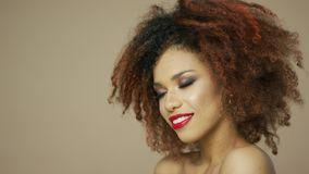 Ethnic woman with red lips touching hair. Portrait of cheerful ethnic woman with red lips touching curly hair and looking at camera in studio stock footage