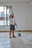 Ethnic worker with roller painting walls. Ethnic worker with a roller painting walls in a big hall Stock Photography