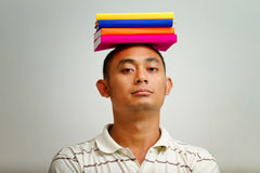 Ethnic young man balance books on head Stock Photos