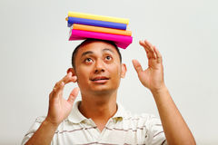 Ethnic young man balancing books on head Stock Images