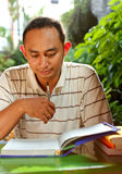 Ethnic young man concentrate study books. Asian ethnic young adult male in front of a desk, studying many literature Stock Photos
