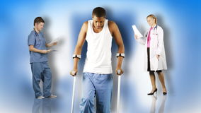 Ethnic young man walking with crutches with doctors in the background footage stock footage