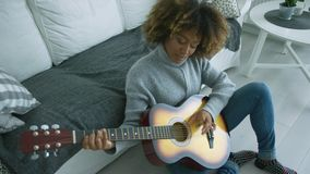 Relaxed woman playing guitar at home stock video