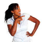 Ethnic young woman pointing and looking right Stock Photos