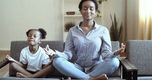 Ethnicity family mindful african mom teaching cute black kid daughter doing yoga exercise at home, calm healthy mixed
