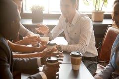 Ethnie multi d'amis buvant du café ensemble en café Images stock