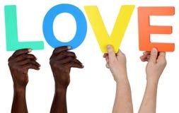 Ethnie multi de personnes tenant l'amour de mot Images stock