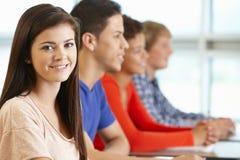 Ethnisch gemischte Jugendschüler in der Klasse, eine lächelnd zur Kamera Stockbild