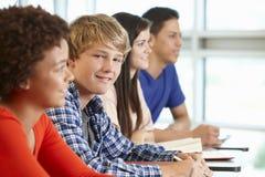 Ethnisch gemischte Jugendschüler in der Klasse, eine lächelnd zur Kamera Stockfotografie