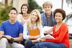 Ethnisch gemischte Studentengruppe, die draußen sitzt Lizenzfreie Stockfotos