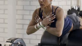 Ethnische afro-amerikanische Frau, die ihren Körper auf einer Übungsmaschine anhebt stock footage